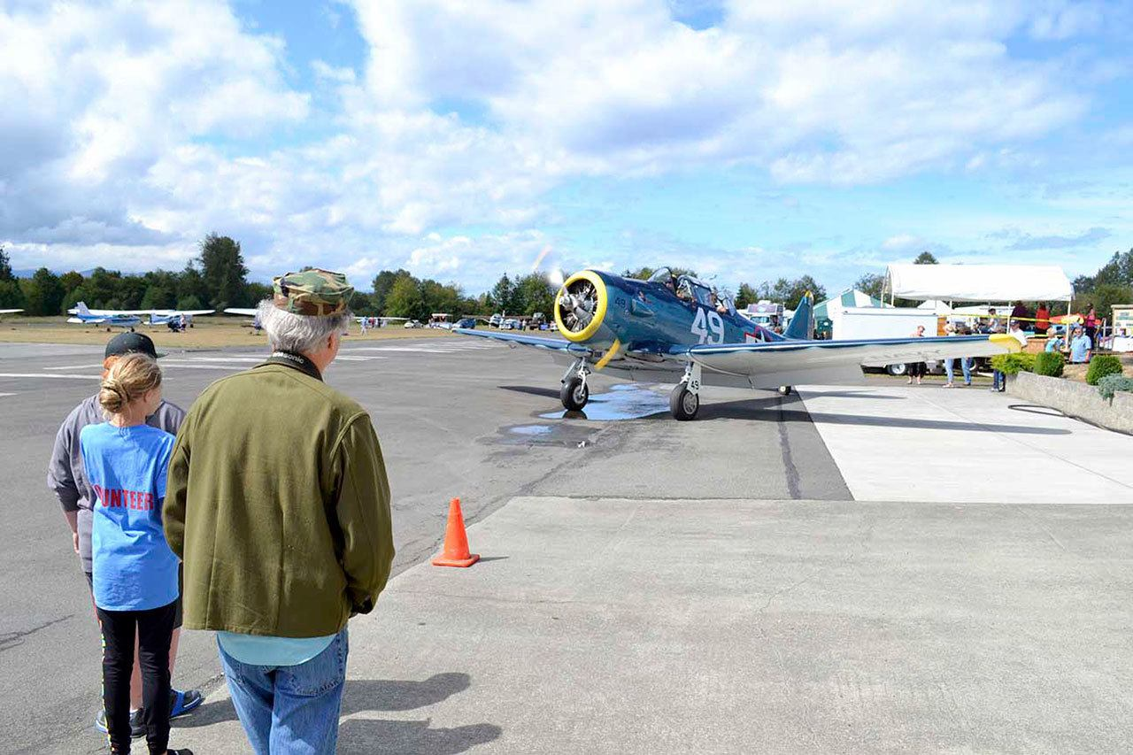 Visitors to the Olympic Peninsula Air Affaire look at the Capt. Johnny Johnson's North American T-6 Texan single-engine advanced trainer aircraft as it arrives last year. Johnson hopes to return to the event Sunday. (Matthew Nash/Olympic Peninsula News Group)