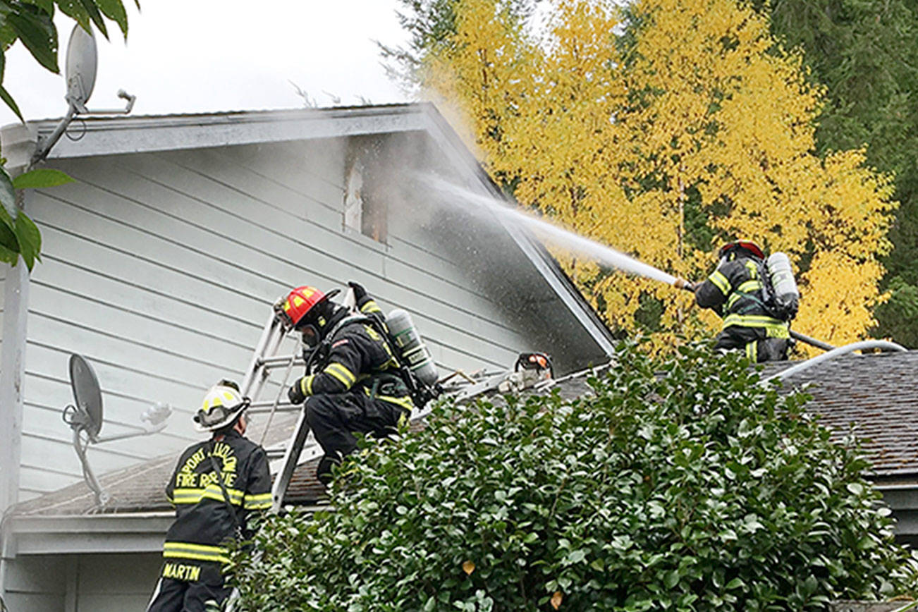 Firefighters spray water at a fire through a window of a residence in the 70 block of Chimacum Creek Road on Monday morning. The fire claimed two pets, a cat and a dog. (East Jefferson Fire & Rescue)