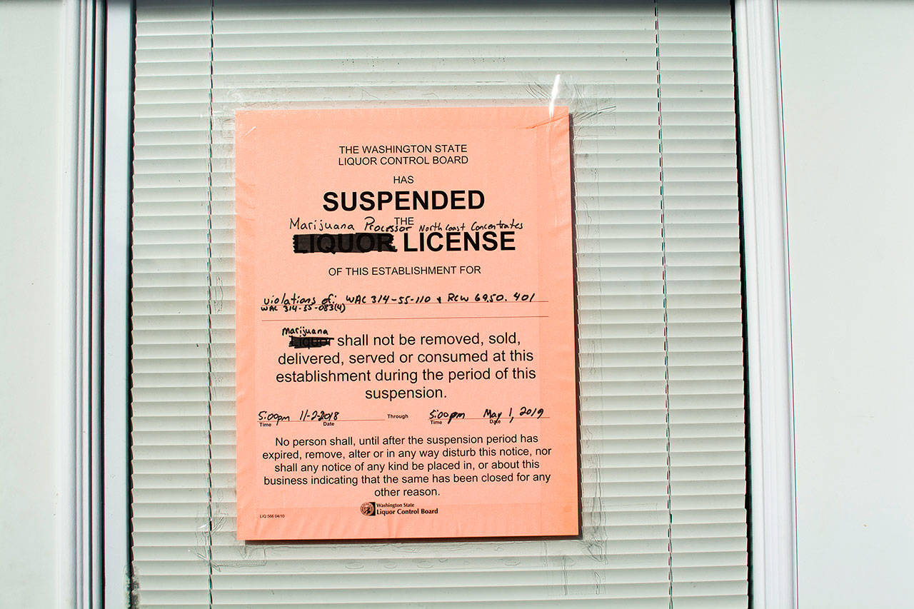 A sign showing the state Liquor and Cannabis Board has suspended the licenses of North Coast Concentrates was taped to the door of the business. (Jesse Major/Peninsula Daily News)