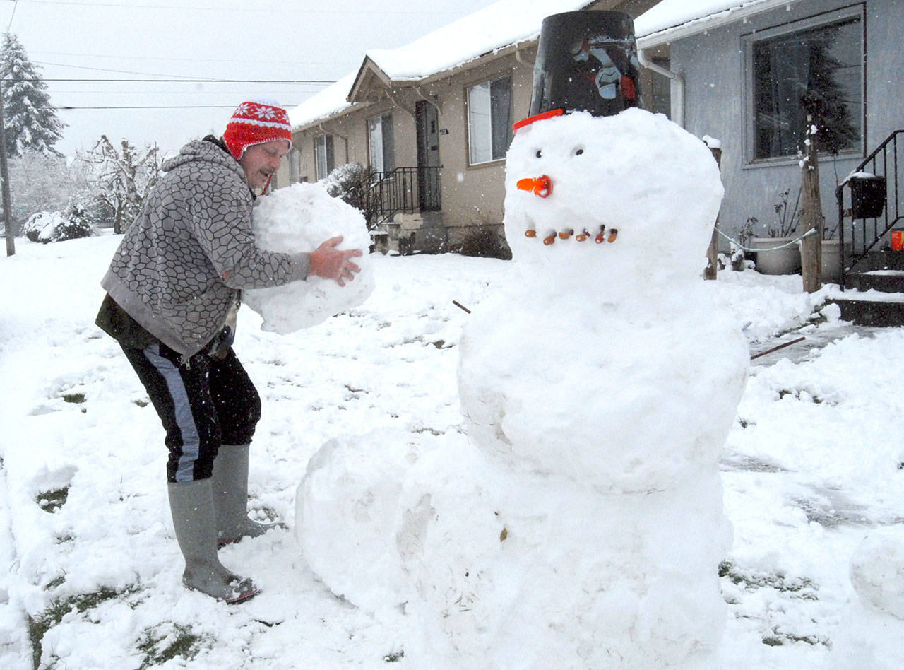 Jeff Bellis of Port Angeles builds a family of snowmen along Cherry Street in Port Angeles on Friday. (Keith Thorpe/Peninsula Daily News)