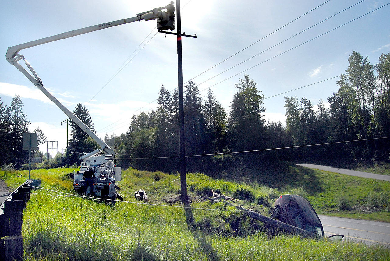 A Clallam County PUD crew repairs power lines on Wednesday morning after a car failed to negotiate a turn at the top of the Tumwater Truck Route early Wednesday morning and toppled a power pole. (Keith Thorpe/Peninsula Daily News)