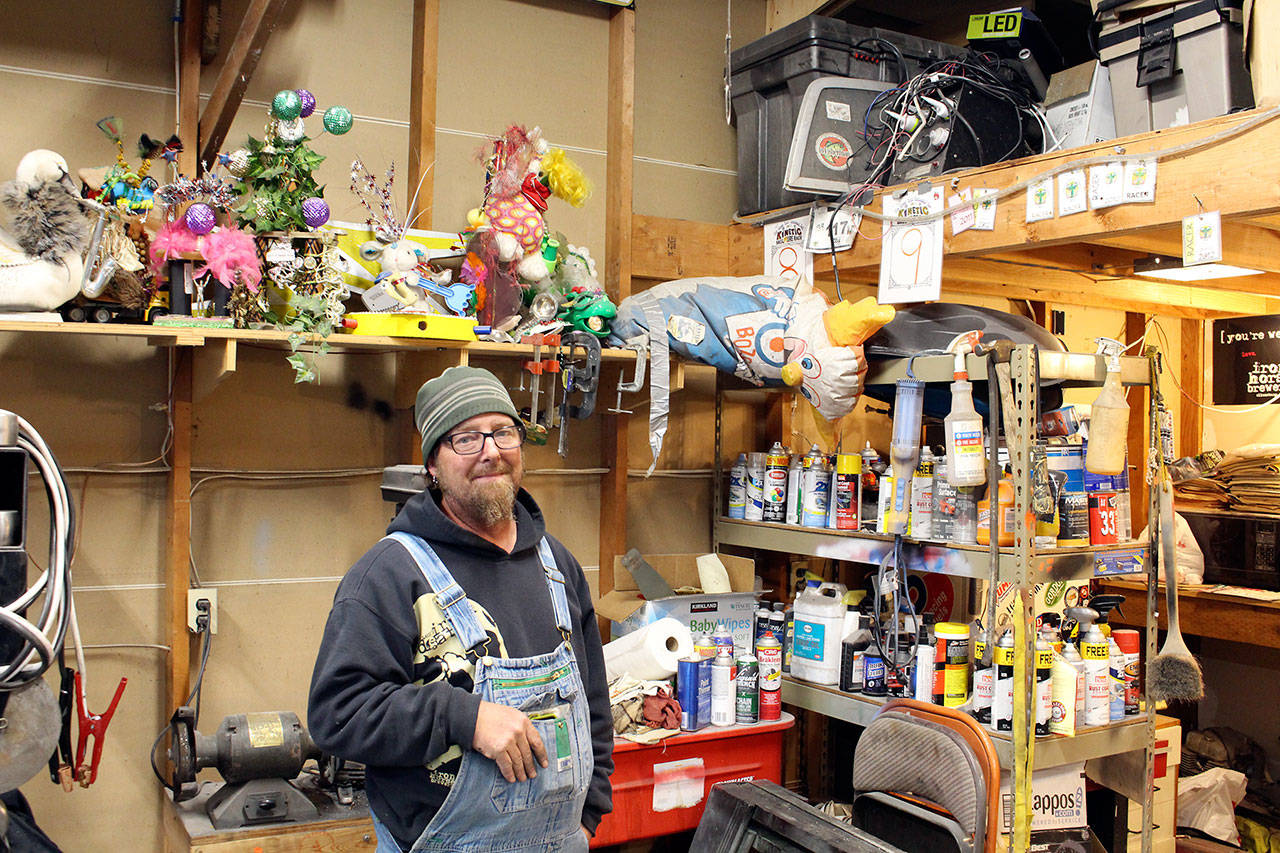 Bertl stands under his shelf of trophies and awards he has earned during his 15-year history of Kinetic Races. (Zach Jablonski/Peninsula Daily News)