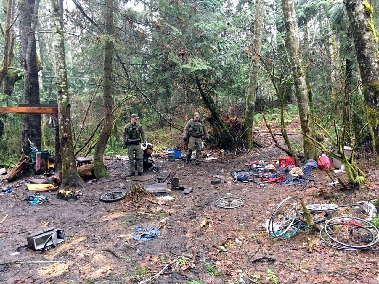 State Department of Fish and Wildlife officers Morgan Cooney and Bryan Davidson survey trash left behind at an illegal homeless encampment. (Washington Department of Fish and Wildlife)