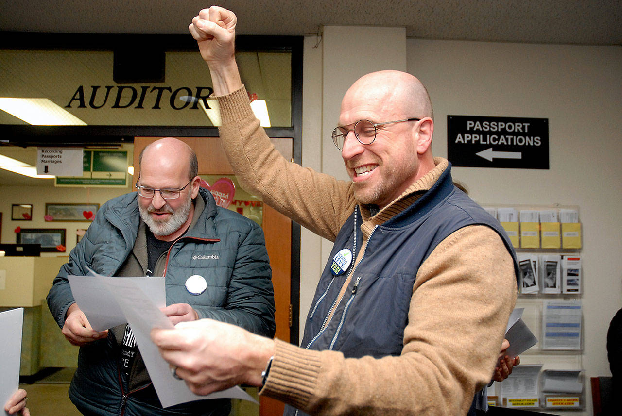 Steve Methner, committee chair for Port Angeles Citizens for Education, right, raises a fist in celebration as fellow committee member Nolan Duce looks over ballot results that showed a capital levy for the Port Angeles School District passing after Tuesday's initial count. (Keith Thorpe/Peninsula Daily News)
