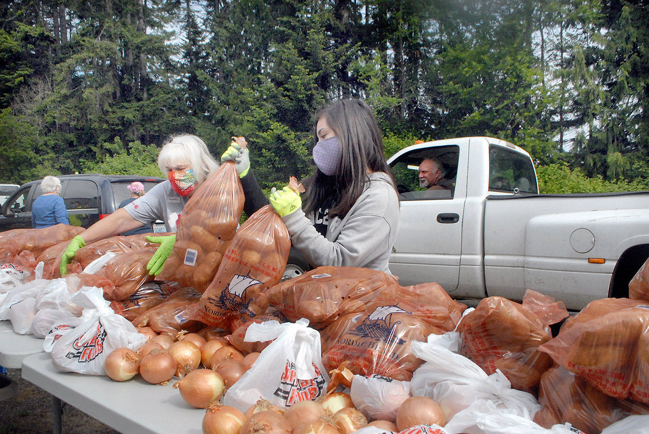 Volunteers Delores Hampton, left, and Tavita Bucio, both of Sequim, pick up bags of potatoes and onions for placement into a waiting vehicle during a giveaway Saturday, May 23, 2020, in the parking lot at the Clallam County Fairgrounds in Port Angeles. Dozens of volunteers distributed a portion of about 50,000 pounds of potatoes and 3 tons of onions during the event, which included a similar giveaway in Forks. (Keith Thorpe/Peninsula Daily News)