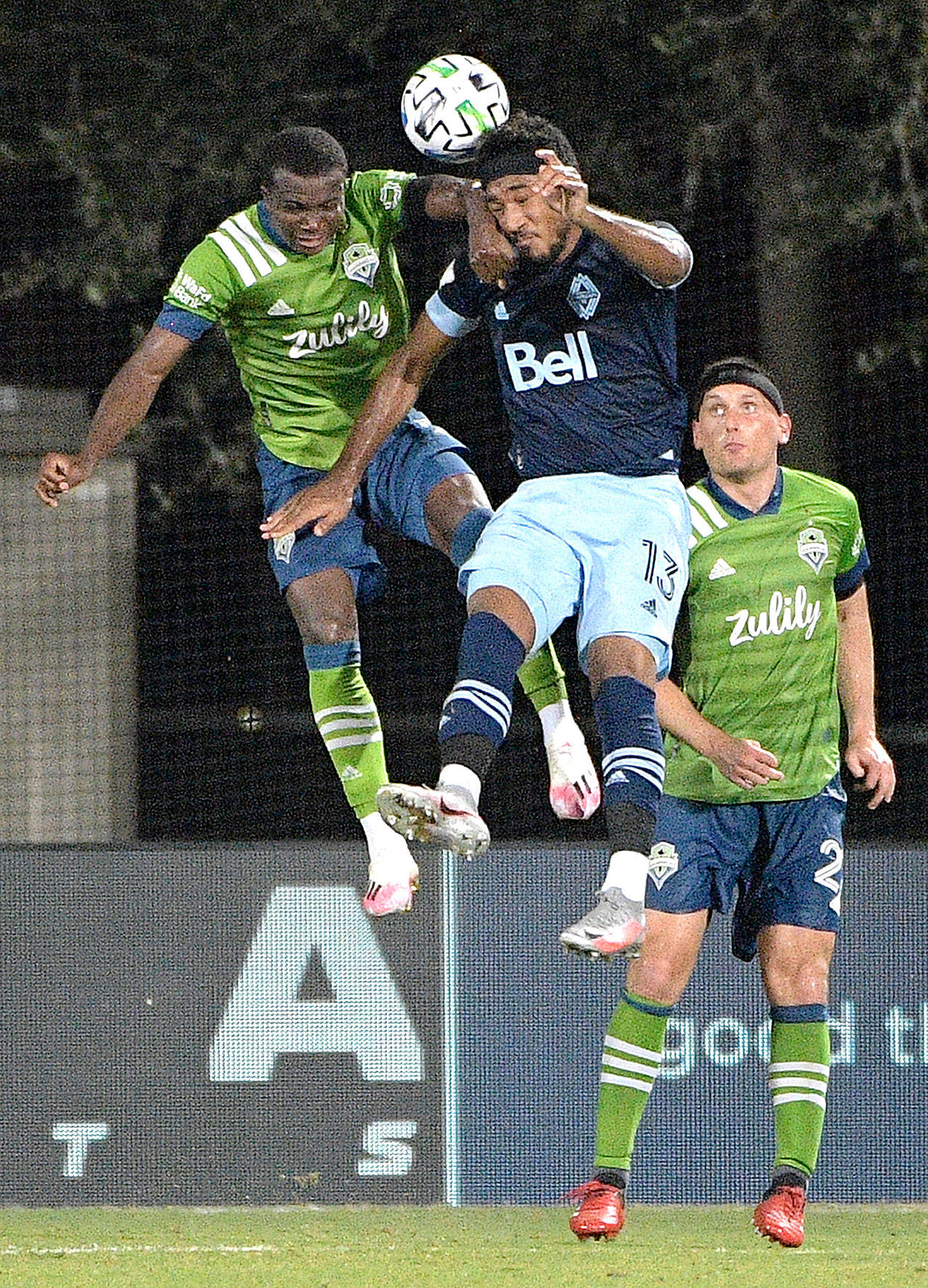 Seattle Sounders defender Shane O'Neill, right, watches as defender Nouhou Tolo, left, and Vancouver Whitecaps defender Derek Cornelius (13) compete for a header during the second half of an MLS soccer match, Monday, July 20, 2020, in Kissimmee, Fla. (AP Photo/Phelan M. Ebenhack)