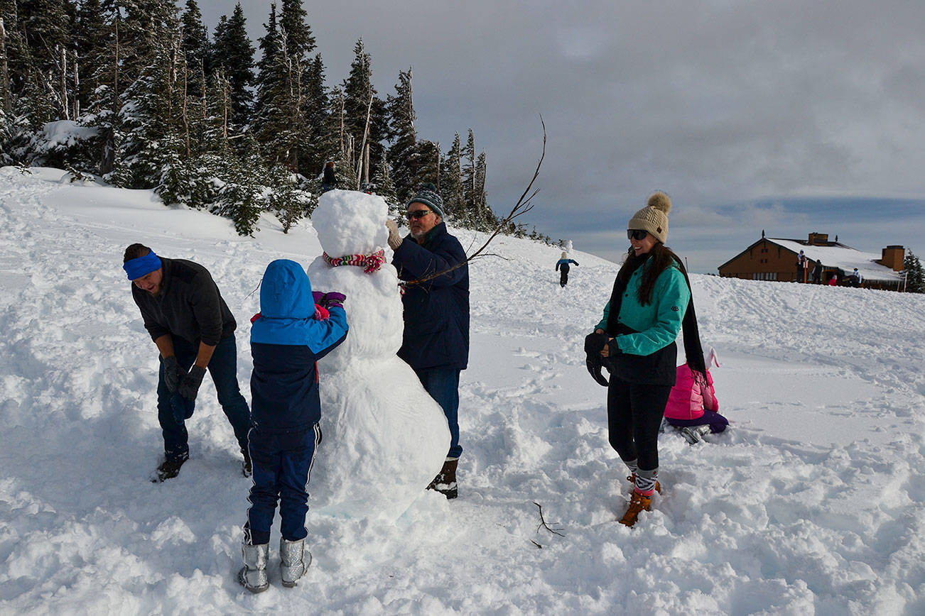 The Roubik Family builds upon a pre-exisiting snowman in the kids' sledding area at Hurricane Ridge on Nov. 27, 2020. From left  is David, Maya, 6, grandfather David, Liz Jones and Vera, 8. (Laura Foster/Peninsula Daily News)