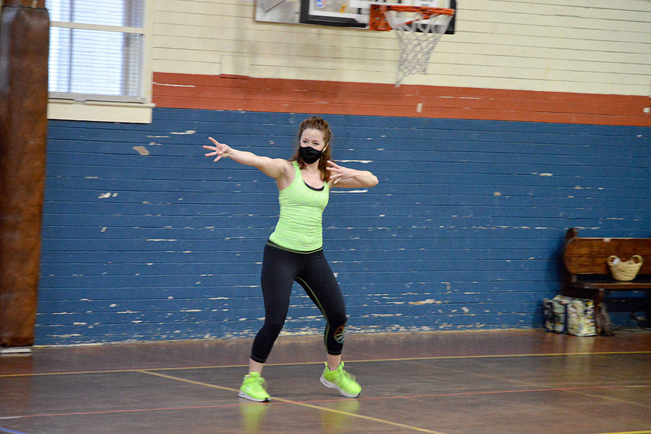 Independent Zumba instructor Bailey Burkhartsmeier teaches a spread-out, masked class for a handful of students at the Port Townsend Community Center on Tuesday morning. Statewide guidelines allowing in-person exercise — with restrictions — are inspiring fitness enthusiasts to come back to gyms and yoga studios this week. (Diane Urbani de la Paz/Peninsula Daily News)