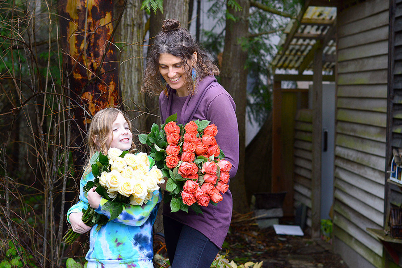 Farmer-florist Lexi Koch of Port Townsend and her son Jude, 8, unwrapped a few dozen roses Thursday for the extra-large floral heart garland to be placed at Haller Fountain on Monday. (Diane Urbani de la Paz/Peninsula Daily News)