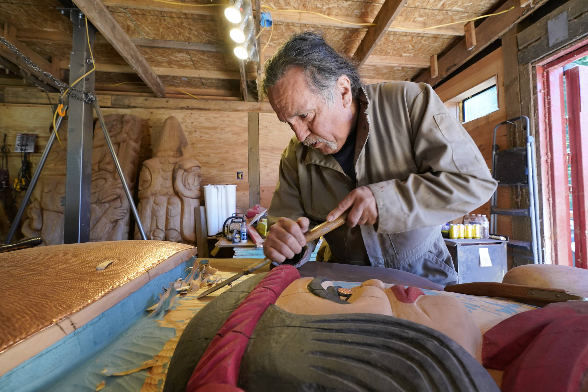 Lummi Nation lead carver Jewell James works on the final details on Monday of a nearly 25-foot totem pole to be gifted to the Biden administration from the Lummi Reservation near Bellingham. The pole, carved from a 400-year-old red cedar, will make a journey from the reservation past sacred indigenous sites before arriving in Washington, D.C., in early June. Organizers said the totem pole is a reminder to leaders to honor the rights of Indigenous people and their sacred sites. (Elaine Thompson/The Associated Press)
