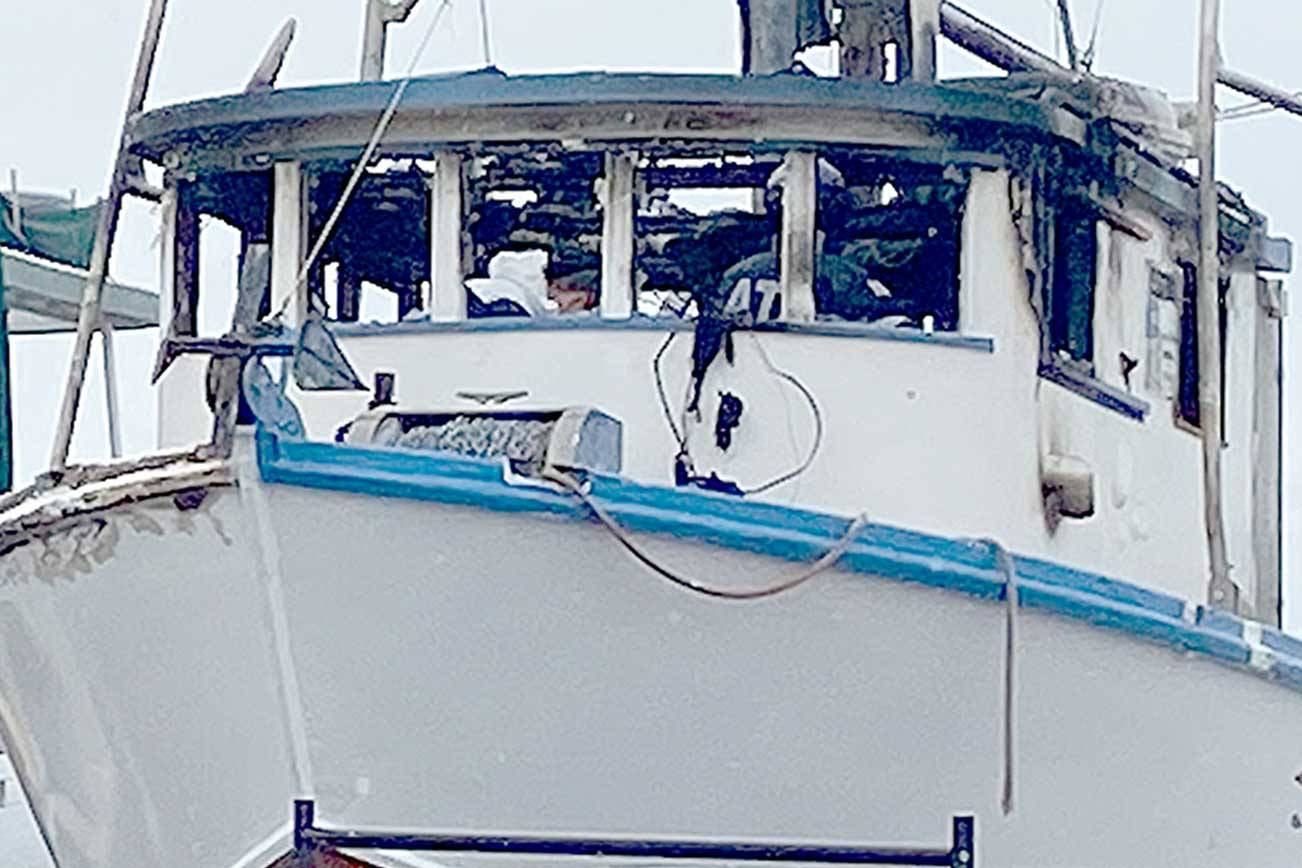 Port Angeles police and the federal Bureau of Alcohol, Tobacco, Firearms and Explosives investigators search the wheelhouse of the Karen L on Sunday. A man was found dead inside the fishing vessel after a fire early Sunday, police said. (Rob Ollikainen/Peninsula Daily News)