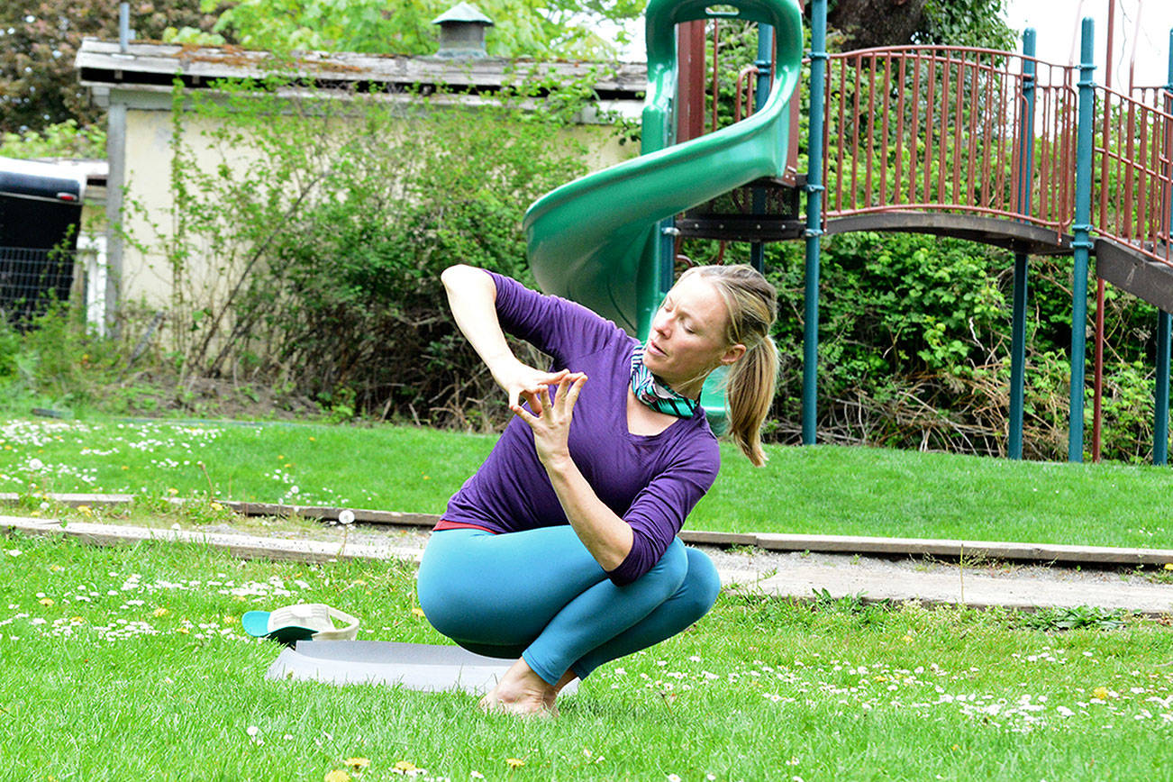 Yoga instructor Karyn Stillwell demonstrates a twisting pose at Port Townsend's Chetzemoka Park on Wednesday. She leads an hour-long yoga practice, weather permitting, at noon Wednesdays and Fridays at the park at Jackson and Blaine streets. (Diane Urbani de la Paz/Peninsula Daily News)