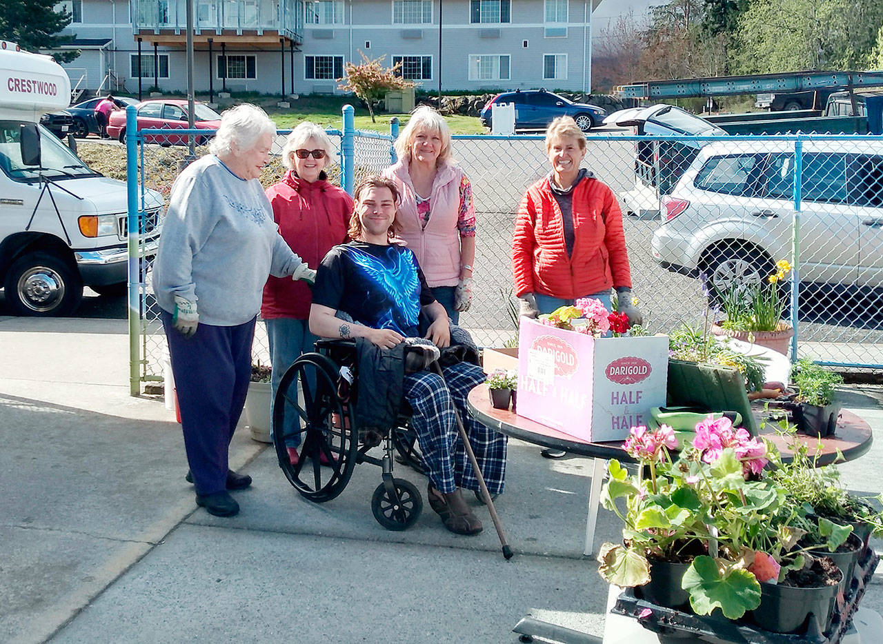 Members of the Port Angeles Garden Club recently gathered for a planting party at Crestwood Health and Rehabilitation. Club members added spring blooms to planters on the residents' patio. Pictured standing, from left to right, are Bernice Cook, Kitty Gross, Shari Bley and Mary Kelsoe. Seated is Crestwood resident Troy Nicholaysen, who will will care for the plantings.