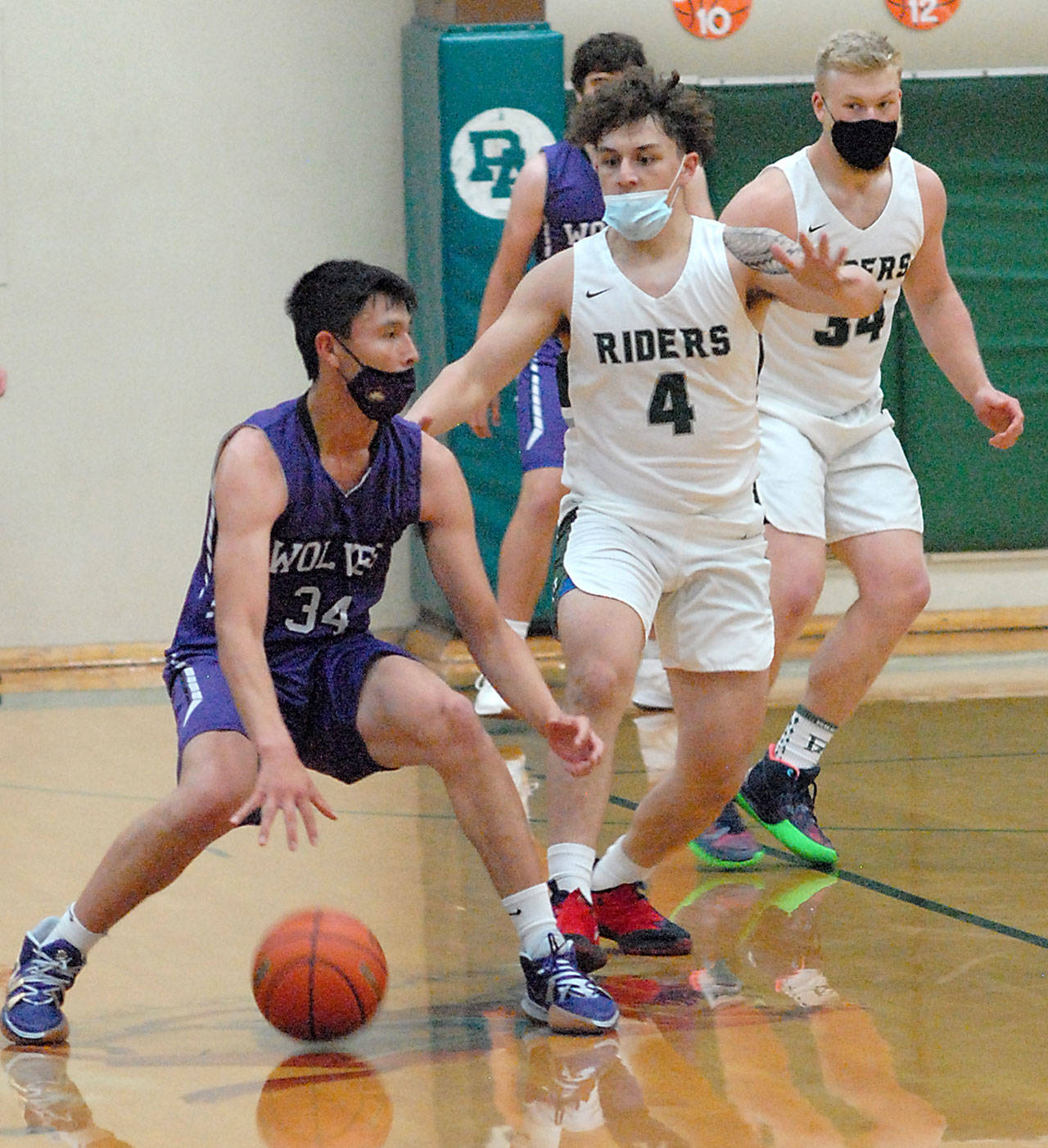 Sequim's Isiah Moore, left, is defended by Port Angeles' Jeremiah Hall, center, and Adam Watkins in the first quarter of play on Wednesday at Port Angeles High School. (Keith Thorpe/Peninsula Daily News)