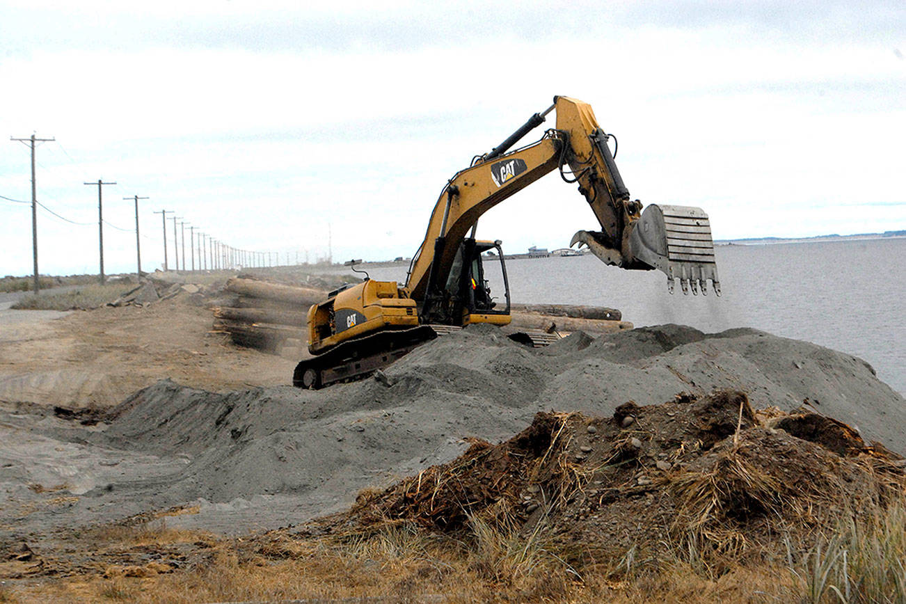 An excavator moves dirt and sand on Ediz Hook on Friday at the former site of the Olympic Peninsula Rowing Association's boat house at the edge of Port Angeles Harbor. (Keith Thorpe/Peninsula Daily News)