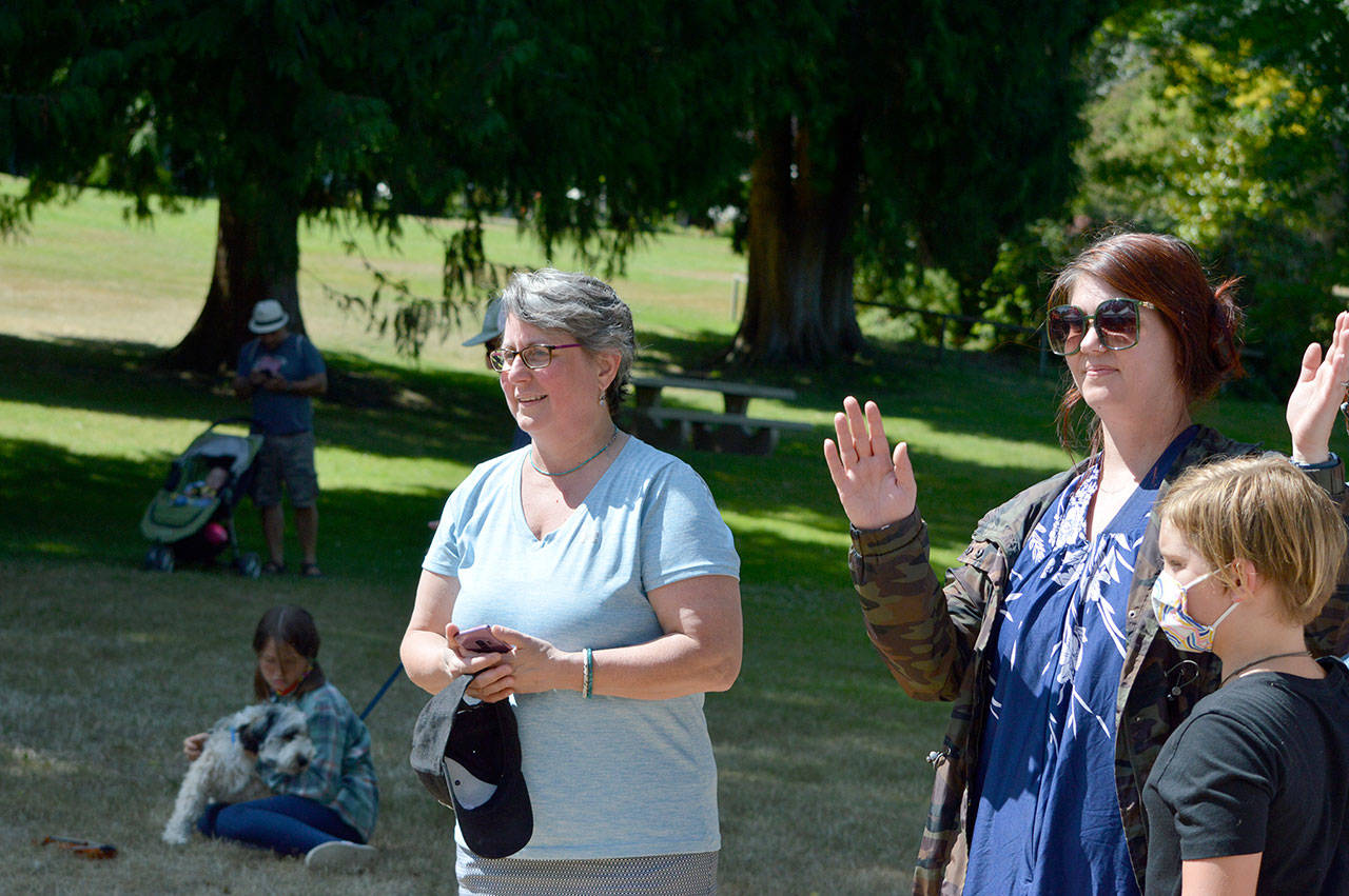 Key City Public Theatre executive artistic director Denise Winter, left, with Tobi McEnerney and her son Argus, 9, watch the youth theater workshop students perform at Chetzemoka Park on Friday. (Diane Urbani de la Paz/Peninsula Daily News)