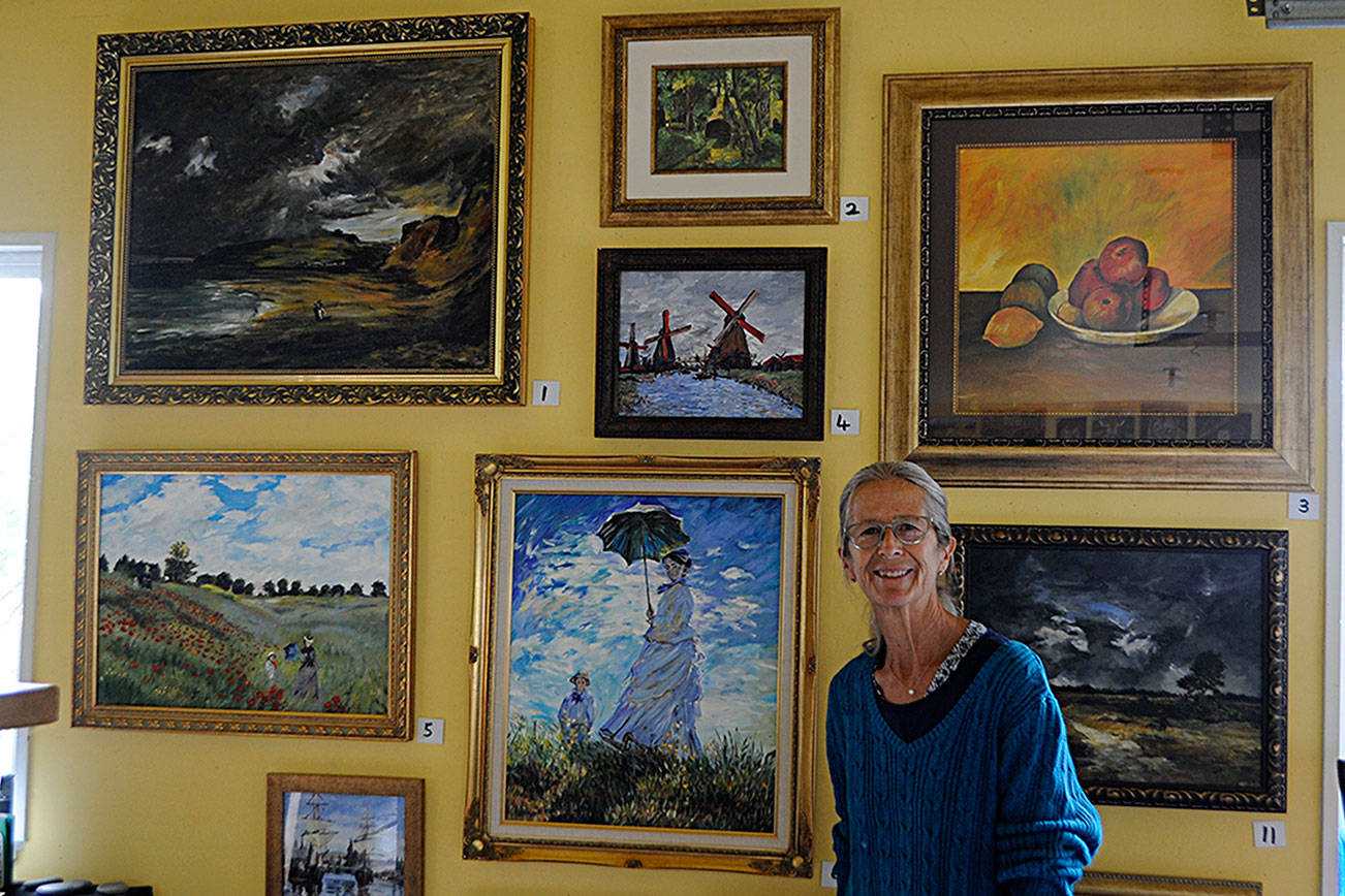 """Carrie Rodlend plans to auction off more than 30 reimagined classic paintings, such as Claude Monet's """"Woman with a Parasol – Madame Monet and Her Son"""" on Saturday from her home studio in Dungeness. She's worked more than a year beside her students on reimagining classic paintings to teach new techniques. Matthew Nash/Olympic Peninsula News Group"""