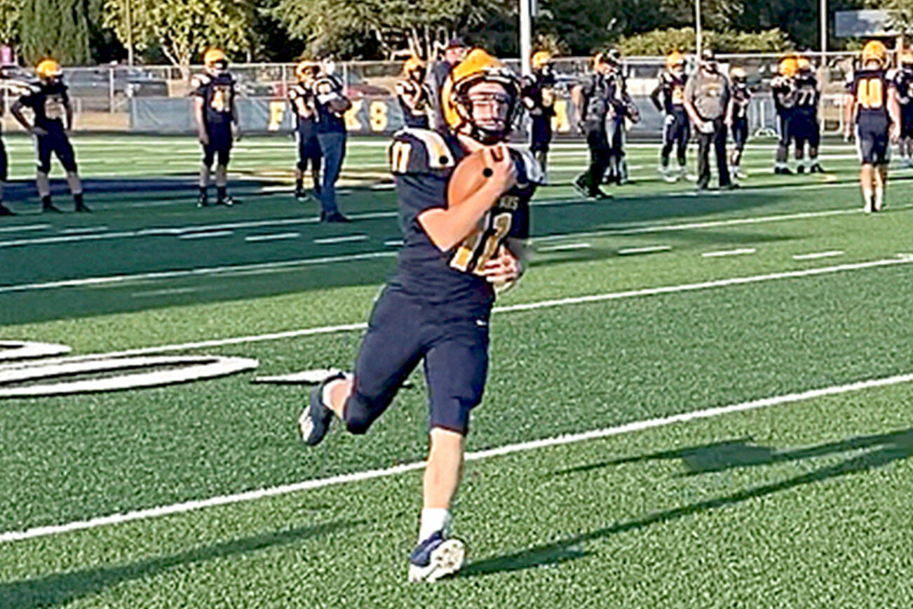 Forks' Kaleb Blanton runs with the ball during pregame warmups before the Spartans' home opener with Sequim last Friday. Blanton and Forks debuted new home uniforms with gold and white shoulder stripes and gold numbers in the game. (Michael Carman/Peninsula Daily News)