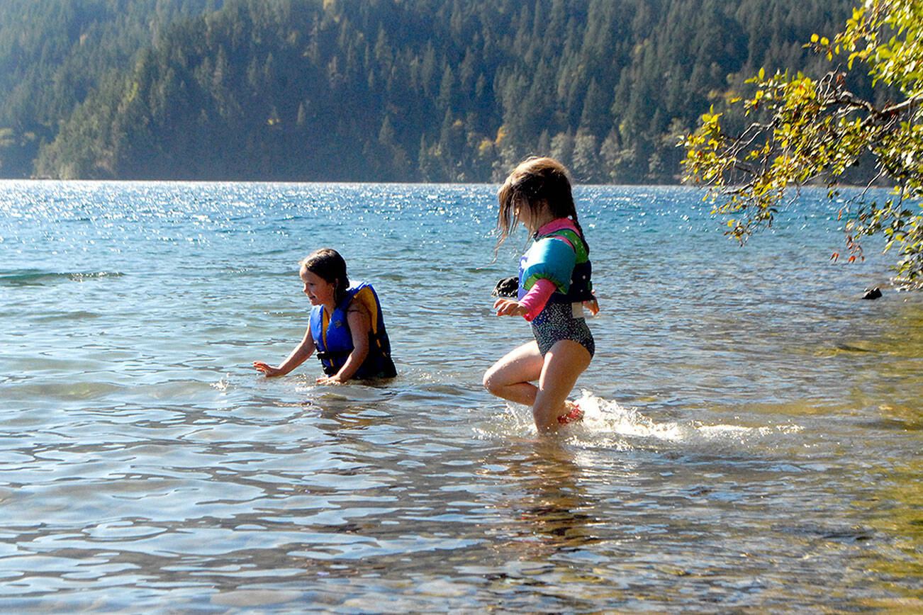 Normajane Goodfellow, 4, left, and Minue Garling, 5, both of Port Angeles, cavort in the waters of Lake Crescent in Olympic National Park over the weekend. The youth were on a family outing to East Beach Road. (Keith Thorpe/Peninsula Daily News)