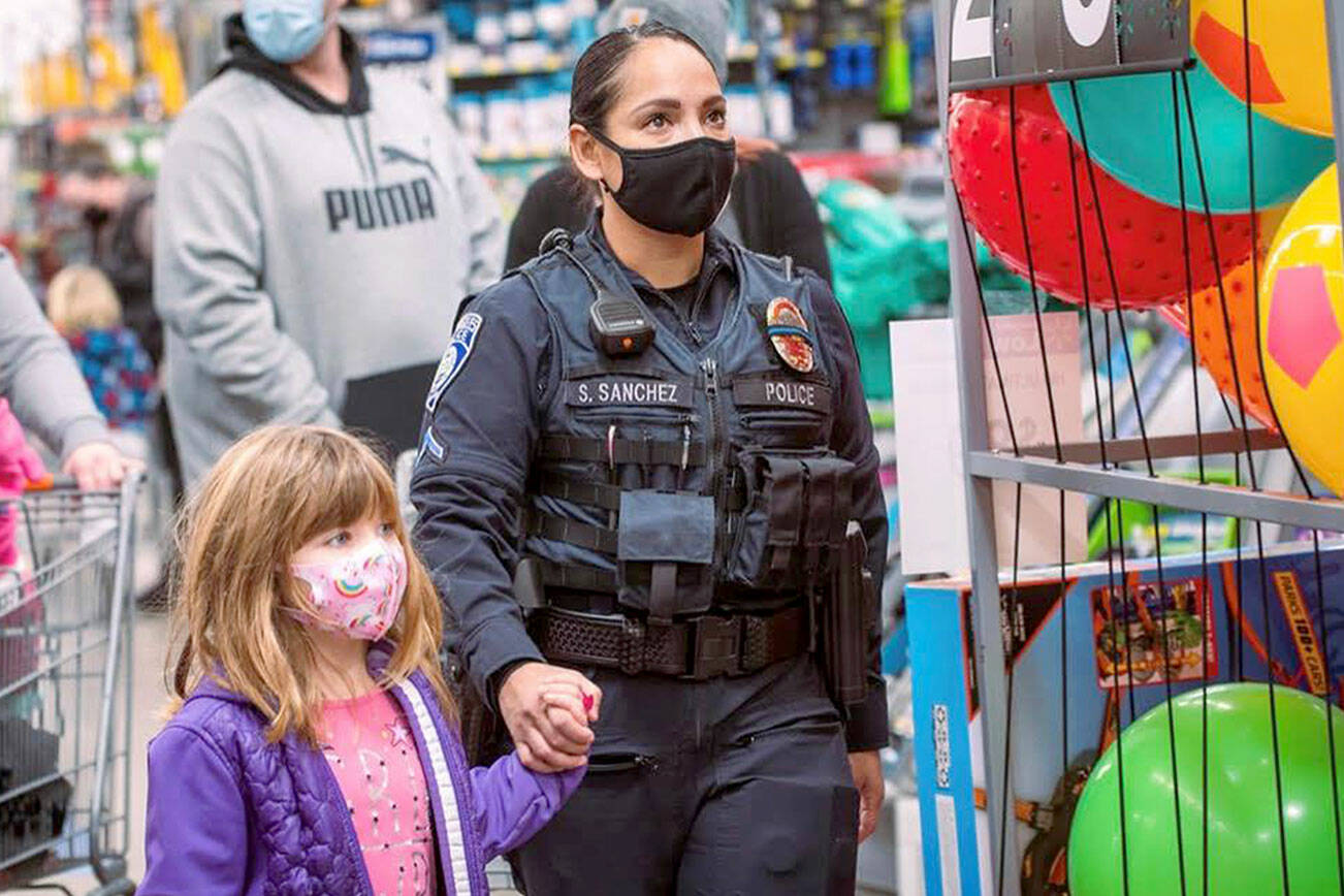 Port Angeles Police Officer Swift Sanchez with a child during a holiday shopping event. The police department is among several agencies in a partnership focused on resiliency throughout October. (Jesse Major Photography)