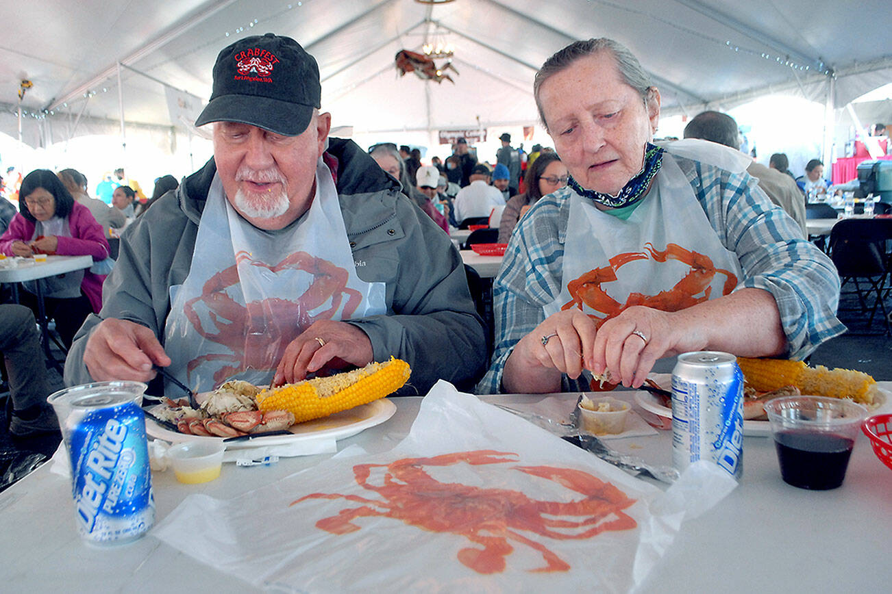Keith Thorpe/Peninsula Daily News Larry and Kathi Hayden of Port Angeles enjoy crab dinners on Friday at the Dungeness Crab and Seafood Festival in Port Angeles.